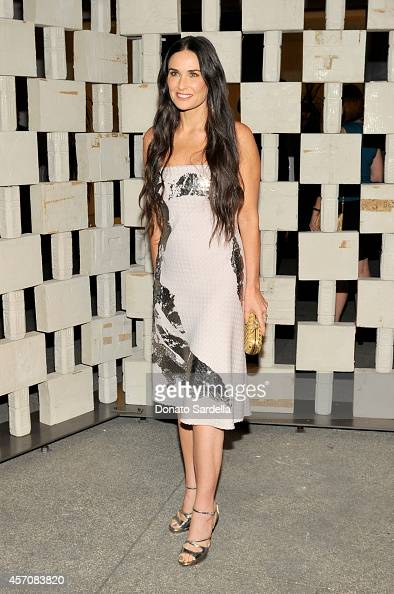 Actress Demi Moore wearing Early Fall 2014 Mist Silver Jacquard Laminated Print Dress and Intreccio Oro Bruciato Knot attends the Hammer Museum's...