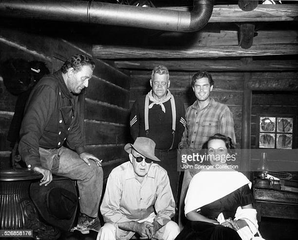 Actress Dolores Del Rio sits beside The Searchers director John Ford Behind them are film cast members John Wayne who plays Ethan Edwards Jack...