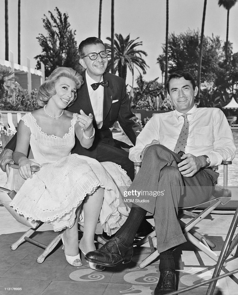 Actress Dolores Gray MGM studio head Dore Schary and actor Gregory Peck sit poolside during the filming of 'Designing Women' at the Beverly Hills...