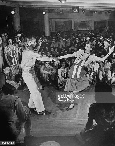 Actress Dorothy McGuire w Amer soldier doing the Lindy in front of onlooking servicemen gals at the American Theater Wing's Stage Door Canteen in the...