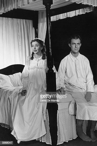 Actress Dulcie Gray and her real life husband and fellow actor Michael Denison sitting on different sides of a four poster bed in a scene from the...