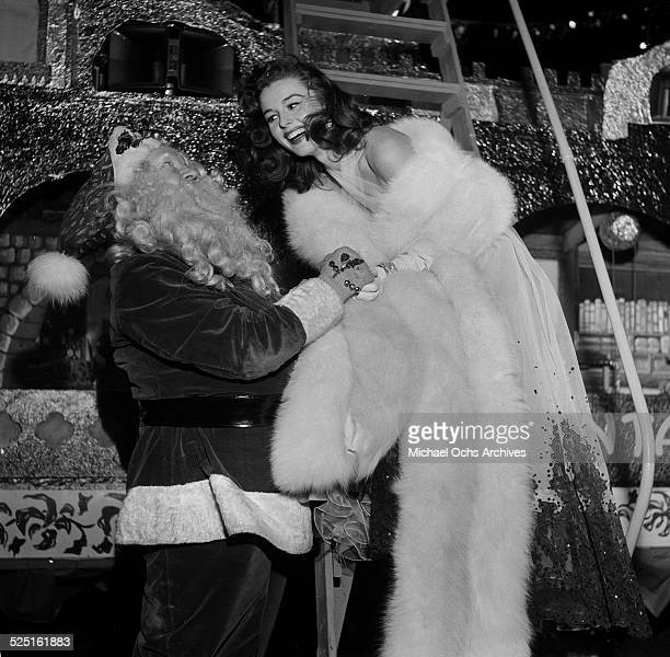 Actress Elaine Stewart poses with Santa Claus during the premiere for 'Knights of the Round Table' in Los AngelesCA