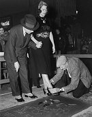 Actress Eleanor Powell has her shoe prints added to cement in front of Grauman's Chinese Theatre with the help of Sid Grauman and Jean W Klossner in...