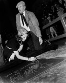 Actress Eleanor Powell signs her name in cement in front of Grauman's Chinese Theatre with the help of Jean W Klossner in Los Angeles California
