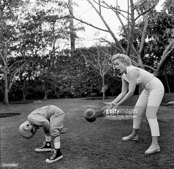 Actress Elena Verdugo plays football with her son Richard at home in Los AngelesCA