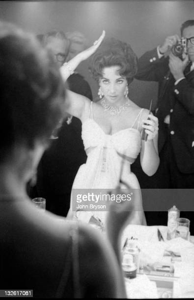 Actress Elizabeth Taylor adjusts her hair in front of the mirror while photographer John Bryson takes a portrait in the background 1959