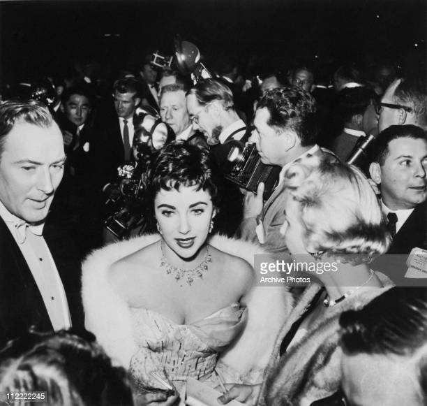 Actress Elizabeth Taylor and her second husband Mike Wilding arrive at a crowded event in formal attire circa 1954