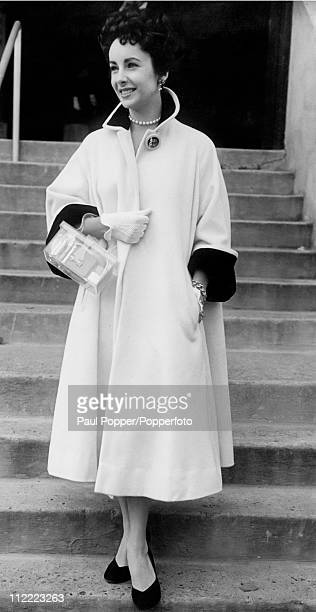 Actress Elizabeth Taylor attending the Wimbledon Tennis championships 25th June 1951 She is wearing a white tent coat with black trim and carries a...