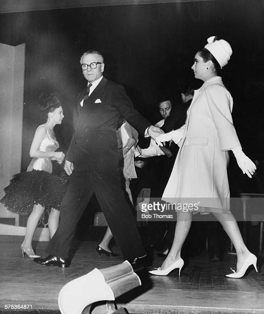 Actress Elizabeth Taylor is led on stage by Sir Laurence Olivier during rehearsals as cohosts of the 'Night of 100 Stars' revue for charity at the...