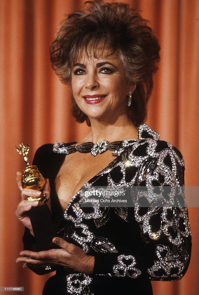 Actress Elizabeth Taylor posing with her Cecil B. DeMille Award for Lifetime Achievement at the 42nd Annual Golden Globe Awards, Los Angeles, California, January 27, 1985.