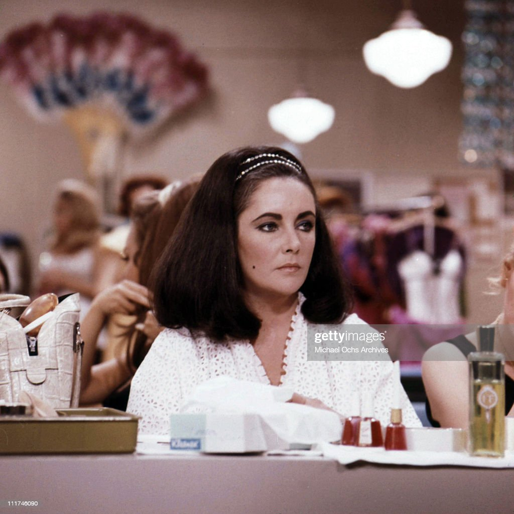 Actress Elizabeth Taylor sitting at a table with bottles of nail polish inside a dressing room on the set of an unidentified film, c. 1970.