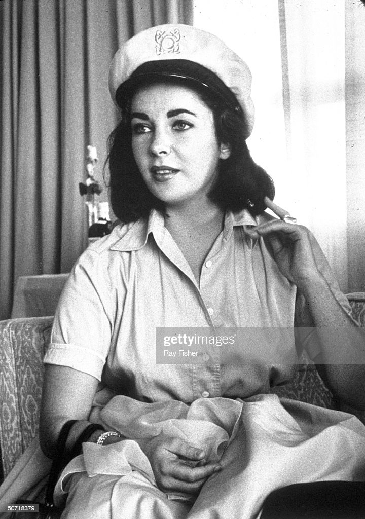 Actress Elizabeth Taylor wearing a captains hat during an interview.