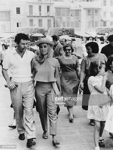 Actress Elizabeth Taylor wearing head scarf and hat arm in arm with her husband singer Eddie Fisher on their honeymoon in Genoa May 22nd 1959