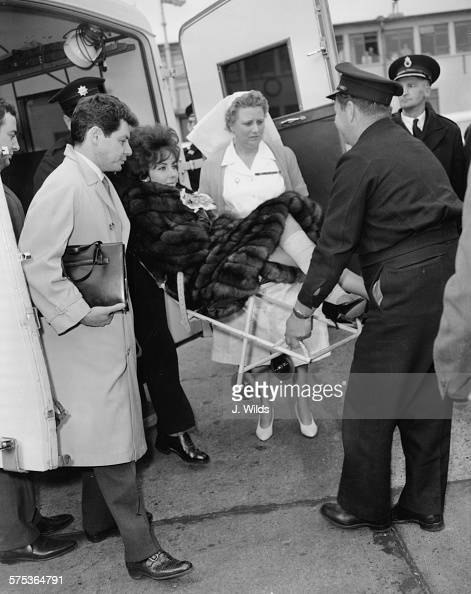 Actress Elizabeth Taylor wears a fur coat as carried from an ambulance at London Airport in a wheelchair on her way to California where she will...