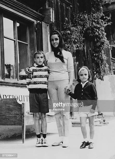 Actress Elizabeth Taylor with her children Chris and Liza window shopping in Gstaad July 1962