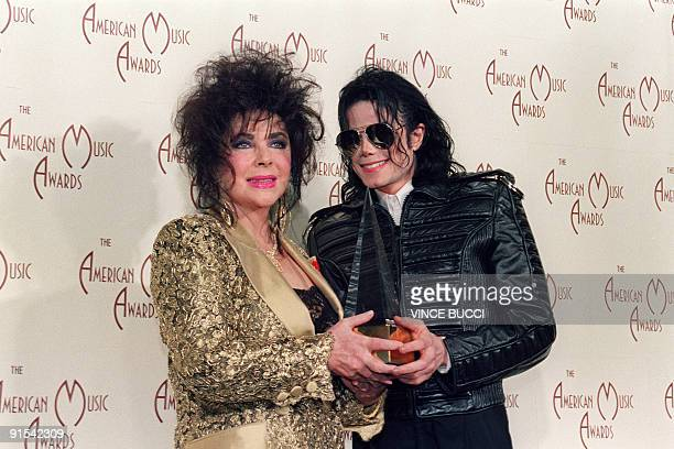US Actress Elizabeth Taylor with singer and performer Michael Jackson hold on one of two awards he won January 25 1993 at the American Music Awards...