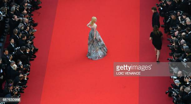 TOPSHOT US actress Elle Fanning poses as she arrives on May 23 2017 for the '70th Anniversary' ceremony of the Cannes Film Festival in Cannes...