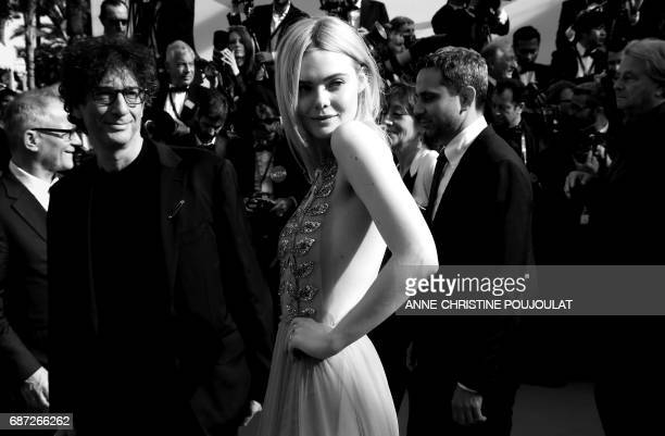 US actress Elle Fanning poses next to British author Neil Gaiman before leaving the Festival Palace on May 21 2017 following the screening of the...