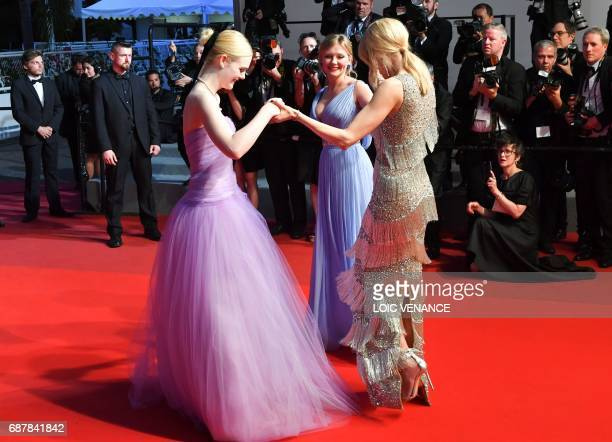 TOPSHOT US actress Elle Fanning US actress Kirsten Dunst and AustralianUS actress Nicole Kidman hold hands as they leave on May 24 2017 following the...