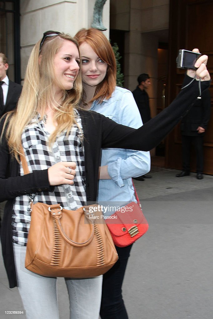 Actress Emma Stone poses with a fan as she is sighted on September 1, 2011 in Paris, France.