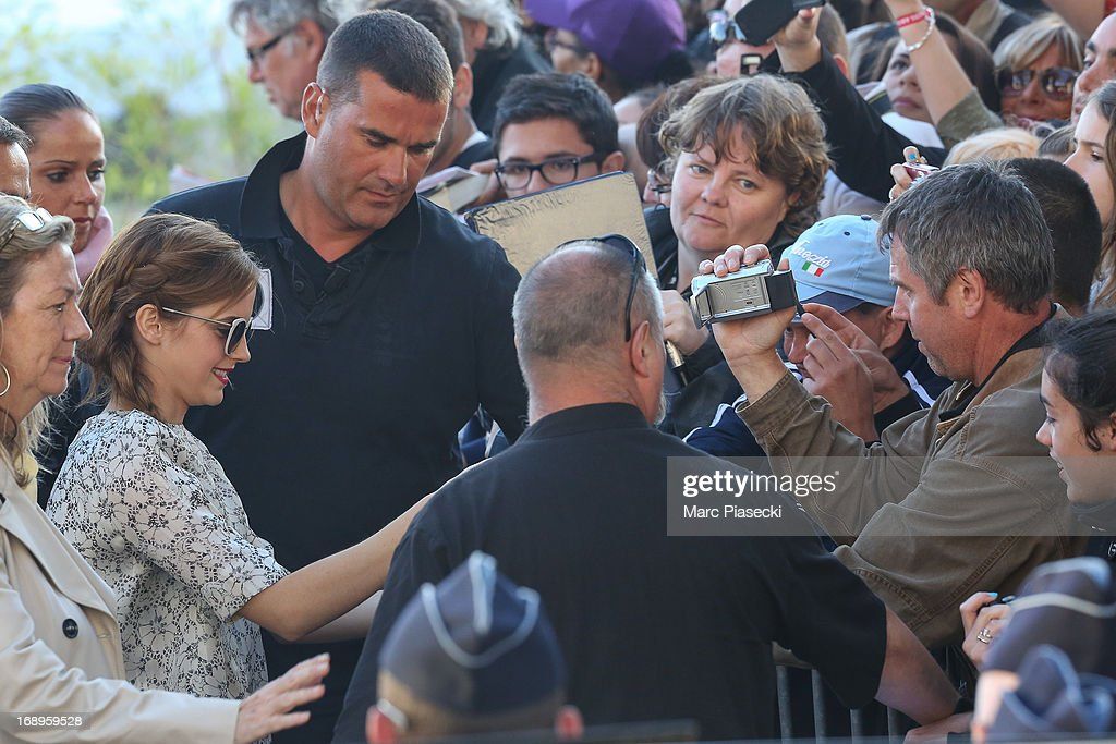 Actress <a gi-track='captionPersonalityLinkClicked' href=/galleries/search?phrase=Emma+Watson&family=editorial&specificpeople=171373 ng-click='$event.stopPropagation()'>Emma Watson</a> signs autographs as she is seen leaving the 'Le Grand Journal' TV show set during the 66th annual Cannes Film Festival on May 17, 2013 in Cannes, France.