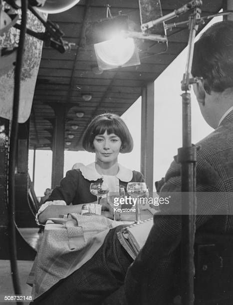 Actress Emmanuelle Riva filming a dinner table scene for the movie 'Therese Desqueyroux' with director Georges Franju guiding her off camera circa...
