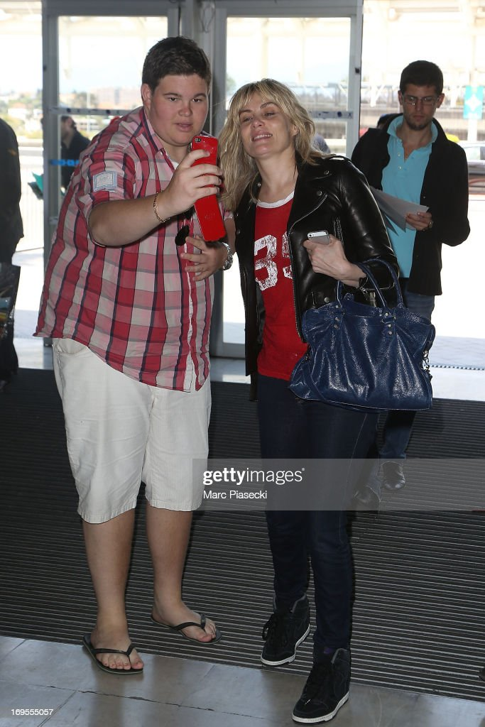 Actress Emmanuelle Seigner poses with french fan as she is sighted at Nice airport after the 66th Annual Cannes Film Festival on May 27, 2013 in Nice, France.