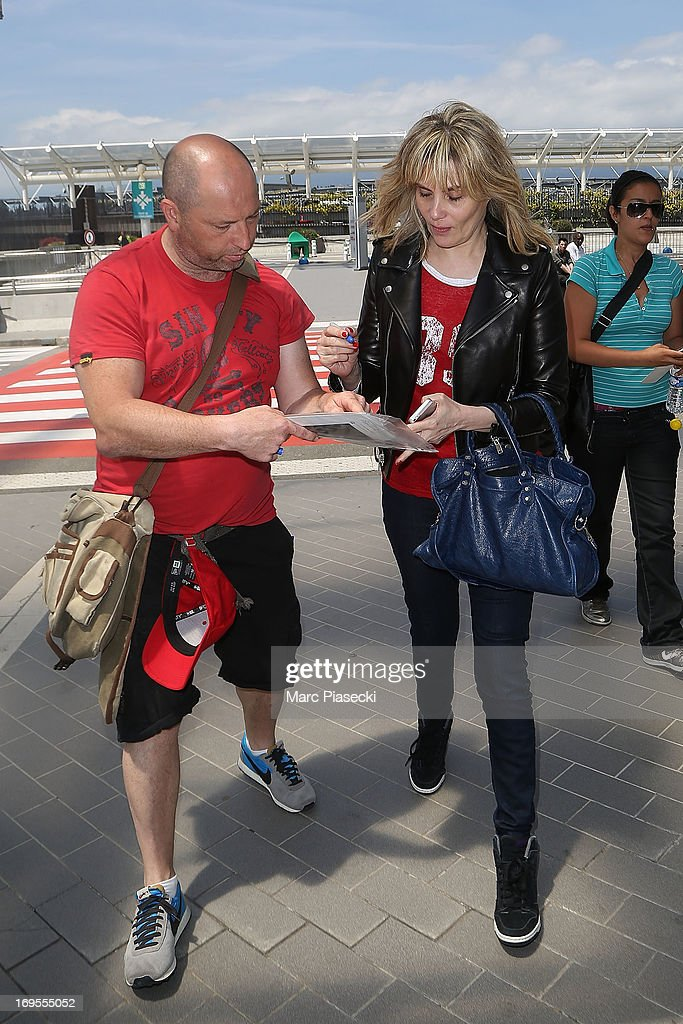 Actress Emmanuelle Seigner signs autographs as she is sighted at Nice airport after the 66th Annual Cannes Film Festival on May 27, 2013 in Nice, France.