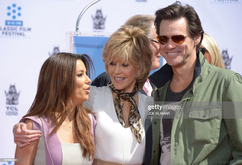 Actress Eva Longoria (L) and actor Jim Carrey (R) attend actress Jane Fonda's (C) Handprint/Footprint Ceremony during the 2013 TCM Classic Film Festival at TCL Chinese Theatre on April 27, 2013 in Los Angeles. Fonda is an American actress, writer, political activist, former fashion model, and fitness guru. She rose to fame in the 1960s with films such as Barbarella and Cat Ballou. She has won two Academy Awards, an Emmy Award, three Golden Globes and received several other movie awards and nominations during more than 50 years as an actress. After 15 years of retirement, she returned to film in 2005 with Monster-in-Law, followed by Georgia Rule two years later. She also produced and starred in over 20 exercise videos released between 1982 and 1995, and once again in 2010. AFP PHOTO/JOE KLAMAR