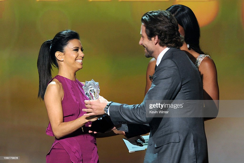 Actress Eva Longoria (L) presents actor Bradley Cooper onstage at the 18th Annual Critics' Choice Movie Awards held at Barker Hangar on January 10, 2013 in Santa Monica, California.