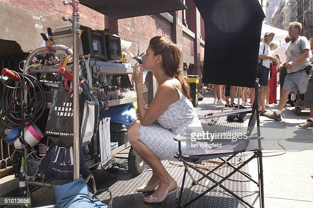 Actress Eva Mendes takes a break and watches herself acting in the last scene on a monitor during the filming of the movie 'Hitch' on the corner of...