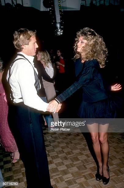 Actress Farrah Fawcett dancing with boyfriend Ryan O'Neal