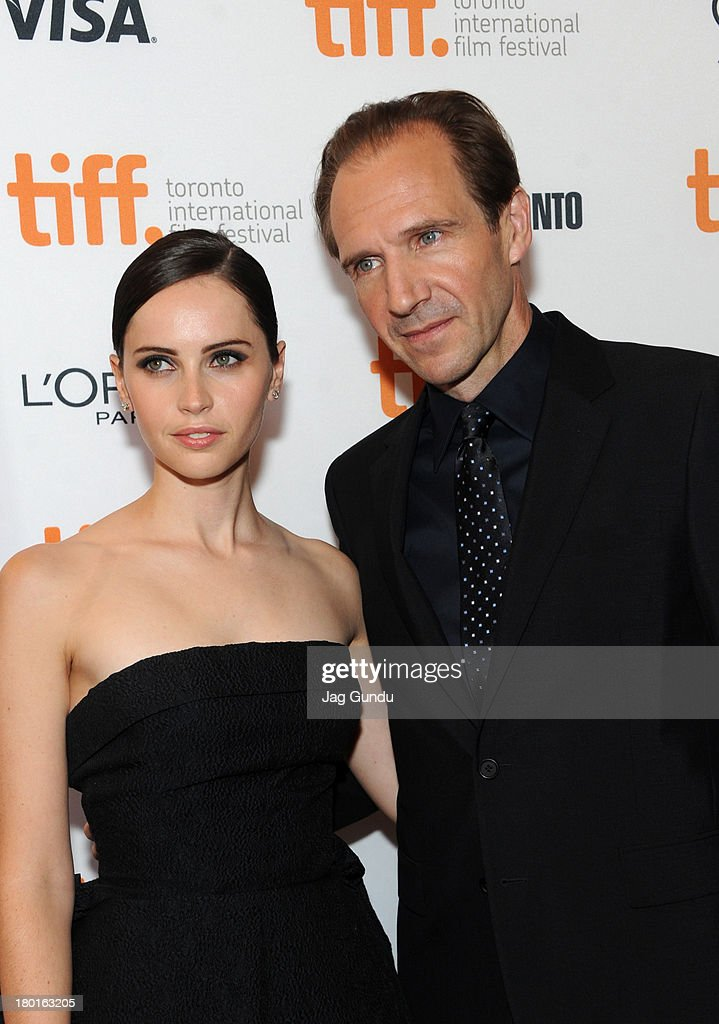 Actress <a gi-track='captionPersonalityLinkClicked' href=/galleries/search?phrase=Felicity+Jones&family=editorial&specificpeople=5128418 ng-click='$event.stopPropagation()'>Felicity Jones</a> and actor/director <a gi-track='captionPersonalityLinkClicked' href=/galleries/search?phrase=Ralph+Fiennes&family=editorial&specificpeople=206461 ng-click='$event.stopPropagation()'>Ralph Fiennes</a> arrive at 'The Invisible Woman' Premiere during the 2013 Toronto International Film Festival at The Elgin on September 9, 2013 in Toronto, Canada.