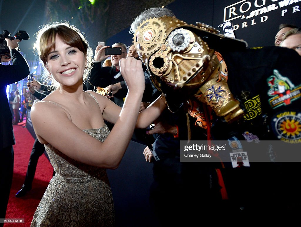 Actress Felicity Jones (L) signs Christopher 'Dude Vader' Canole's helmet at The World Premiere of Lucasfilm's highly anticipated, first-ever, standalone Star Wars adventure, 'Rogue One: A Star Wars Story' at the Pantages Theatre on December 10, 2016 in Hollywood, California.
