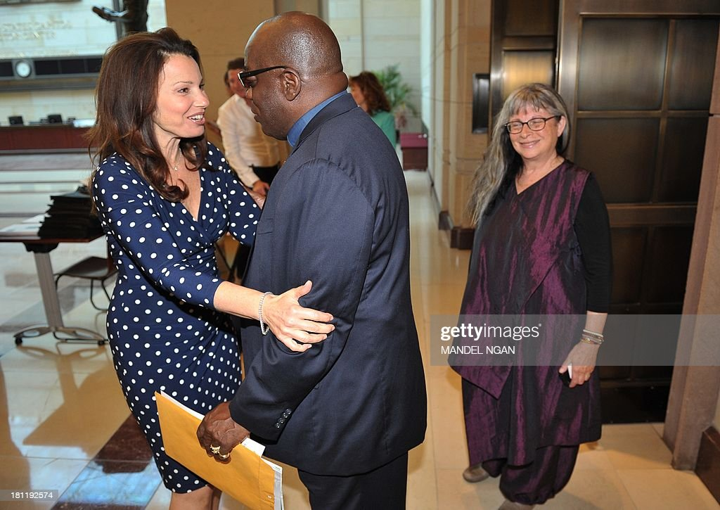 Actress Fran Drescher, founder of Cancer Schmancer, greets an unidentified man as she arrives for a discussion on environmental exposure to carcinogens and a film screening of a documentary titled 'Unacceptable Levels' in the Capitol Visitors Center on September 19, 2013 in Washington, DC. AFP PHOTO/Mandel NGAN
