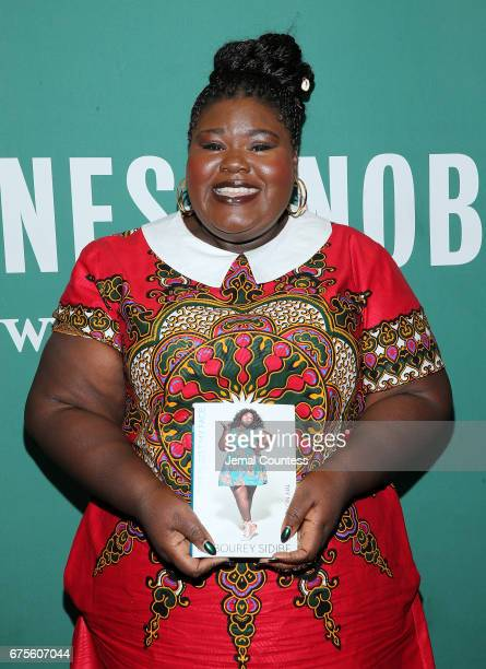 Actress Gabourey Sidibe poses for a photo with a copy of her new book 'This Is Just My Face Try Not To Stare' during an instore appearance at Barnes...