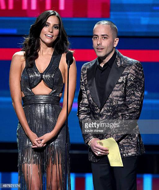 Actress Genesis Rodriguez and recording artist Yandel speak onstage during the 16th Latin GRAMMY Awards at the MGM Grand Garden Arena on November 19...