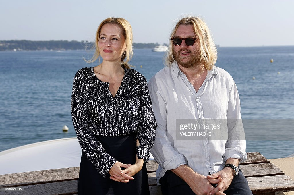 US actress Gillian Anderson (L) and scenarist Allan Cubitt (R) pose during a photocall for the tv series'The Fall' as part of the Mipcom international audiovisual trade show at the Palais des Festivals, in Cannes, southeastern France, on October 8, 2012.