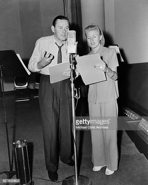 Actress Ginger Rogers and actor Herbert Marshall record in a studio in Los Angeles California