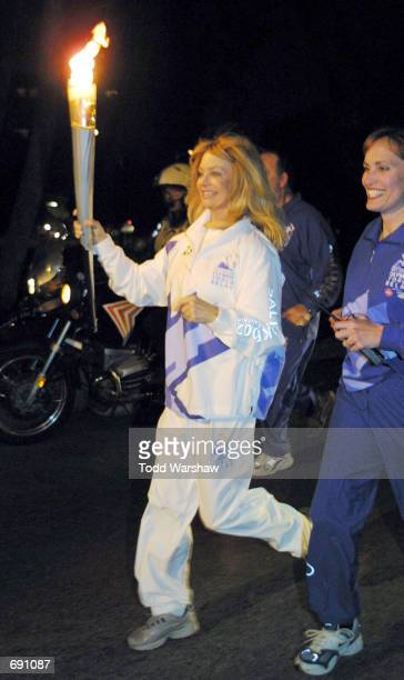 Actress Goldie Hawn carries the Olympic Flame during the 2002 Salt Lake Olympic Torch Relay January 15 2002 in Los Angeles CA