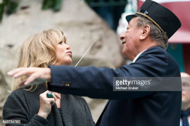 Actress Goldie Hawn conducts a band next to Richard Lugner during an autograph session at Lugner City on February 22 2017 in Vienna Austria