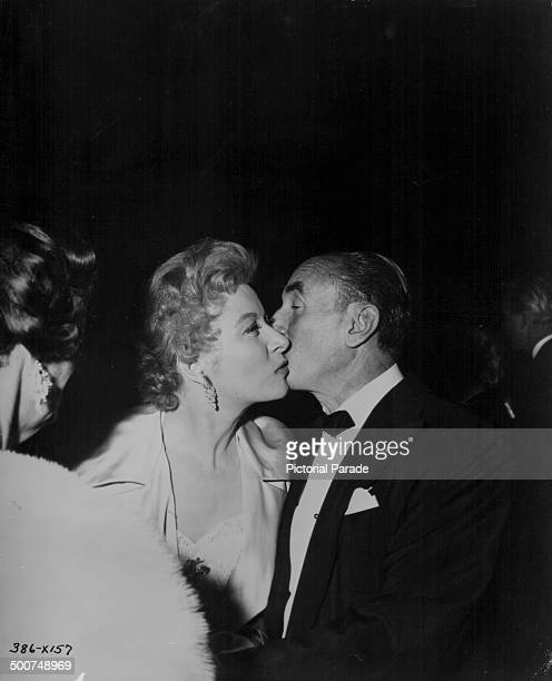 Actress Greer Garson and producer J L Warner kissing at the premiere of the movie 'A Star is Born' 1954