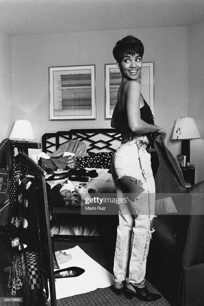 Actress <a gi-track='captionPersonalityLinkClicked' href=/galleries/search?phrase=Halle+Berry&family=editorial&specificpeople=201726 ng-click='$event.stopPropagation()'>Halle Berry</a> in black brassiere & ripped jeans featuring revealingly strategic holes at hip & knee, trying on outfits in cluttered bedroom of her hotel room.