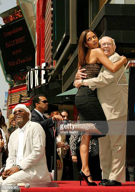 Actress Halle Berry is hugged by honorary mayor of Hollywood Johnny Grant as actor Samuel L Jackson looks on as they attend the ceremony honoring her...
