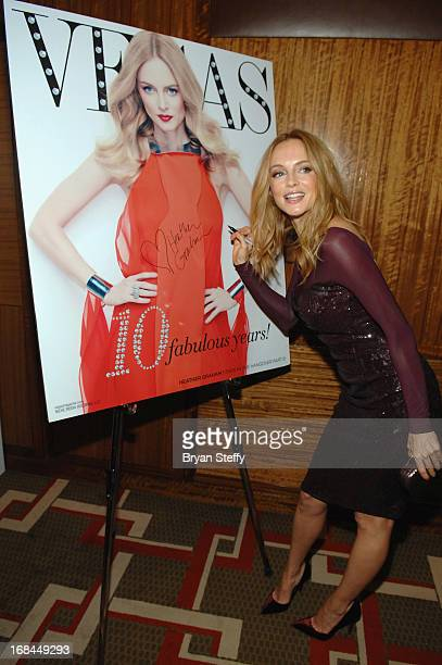 Actress Heather Graham signs an image of her Vegas Magazine cover as she arrives at Vegas Magazine's 10th anniversary celebration at Mandarin...