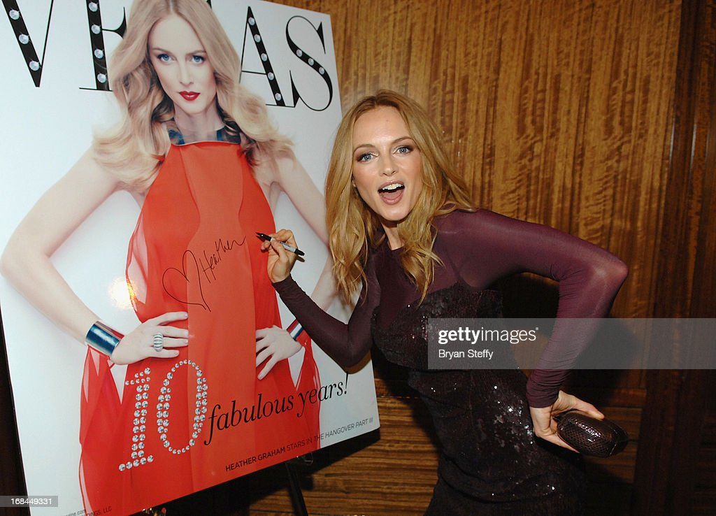Actress <a gi-track='captionPersonalityLinkClicked' href=/galleries/search?phrase=Heather+Graham+-+Actress&family=editorial&specificpeople=204520 ng-click='$event.stopPropagation()'>Heather Graham</a> signs an image of her Vegas Magazine cover as she arrives at Vegas Magazine's 10th anniversary celebration at Mandarin Oriental, Las Vegas at CityCenter on May 9, 2013 in Las Vegas, Nevada.