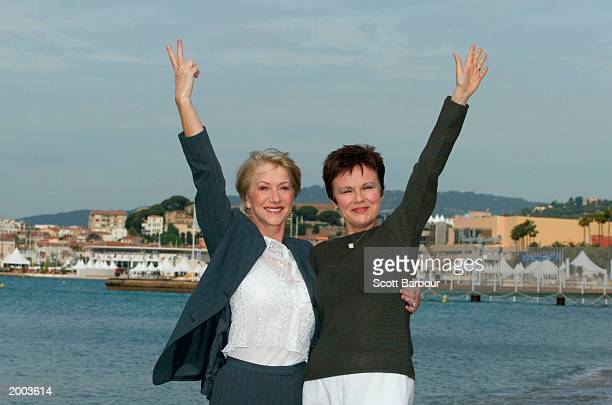 Actress Helen Mirren puts two fingers up in jest as she poses for the cameras with Actress Julie Walters during a photocall for the film 'Calendar...