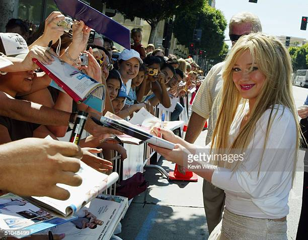Actress Hilary Duff signs autographs as she arrives at the premiere of Warner Bros 'A Cinderella Story' on July 10 2004 at the Chinese Theatre in Los...
