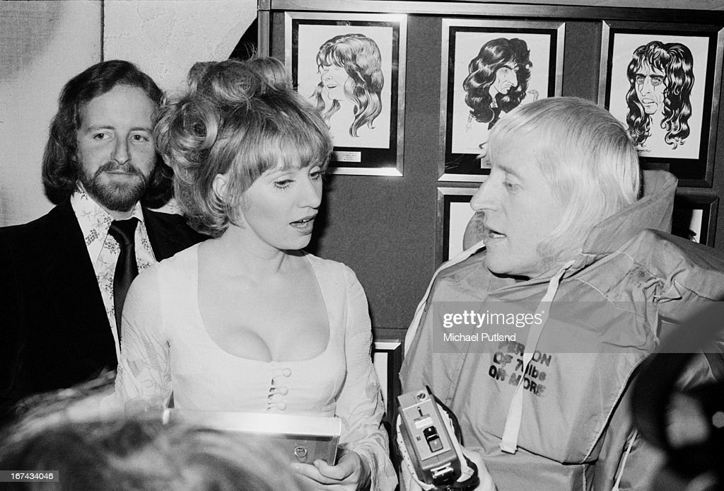 Actress Hilary Pritchard (1942 - 1996) with English disc jockey <a gi-track='captionPersonalityLinkClicked' href=/galleries/search?phrase=Jimmy+Savile&family=editorial&specificpeople=229032 ng-click='$event.stopPropagation()'>Jimmy Savile</a> (1926 - 2011, right) at the Disc And Music Echo music magazine awards, London, 14th February 1973. Behind them are framed caricatures of Maggie Bell (left) and Alice Cooper.