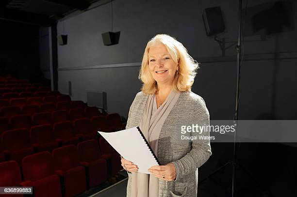 Actress holding script on stage.
